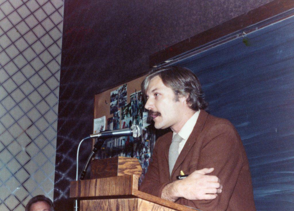 Reville at podium wearing brown sports jacket