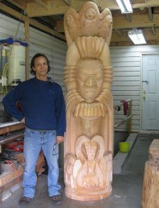 Photo of Ya'Ya Heit standing beside carved wooden sculpture with Indigenous west coast mythical representations of animals.