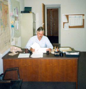 Reville sitting at office desk