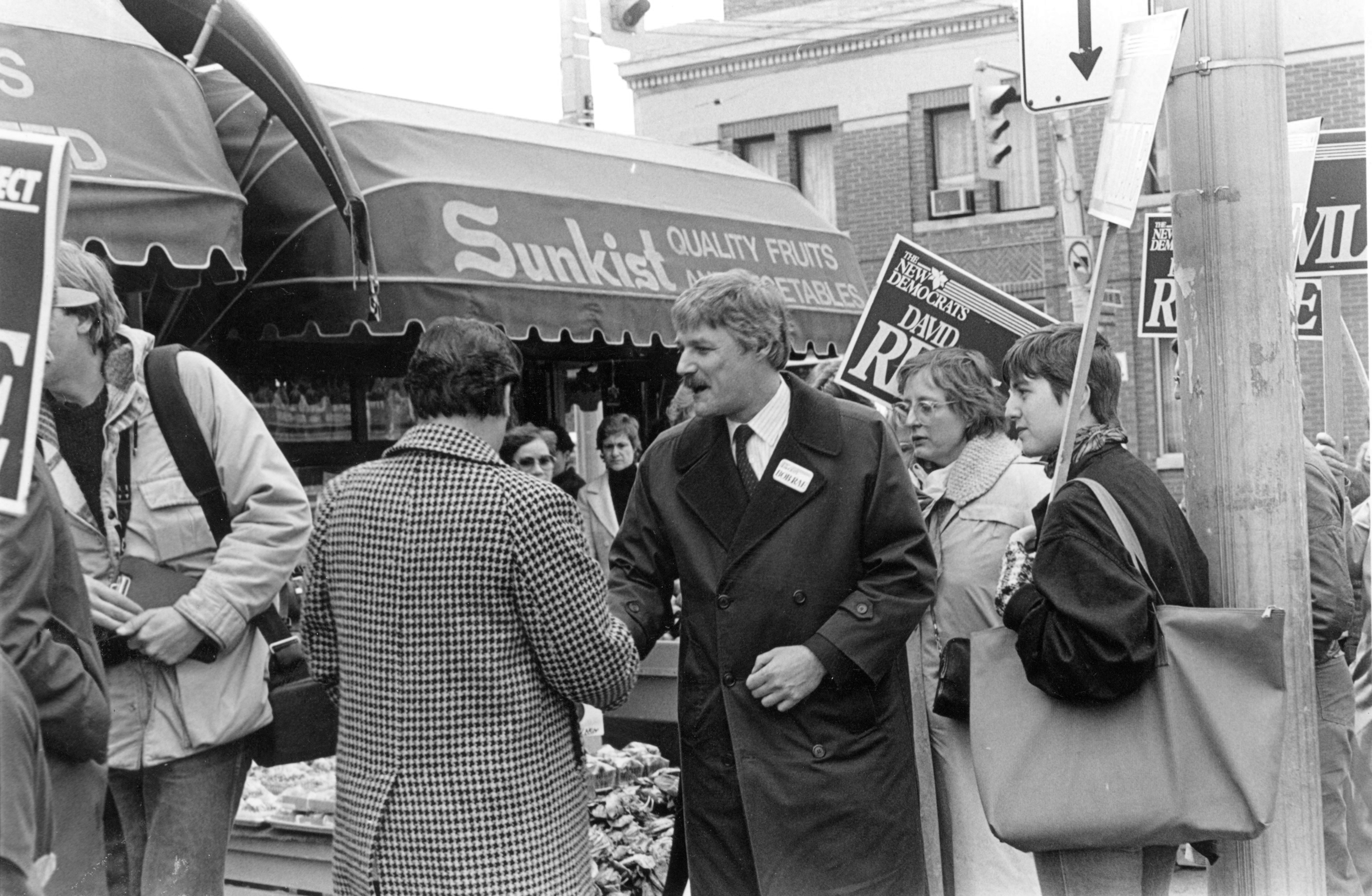 Reville shaking hands with people on street in front of shops