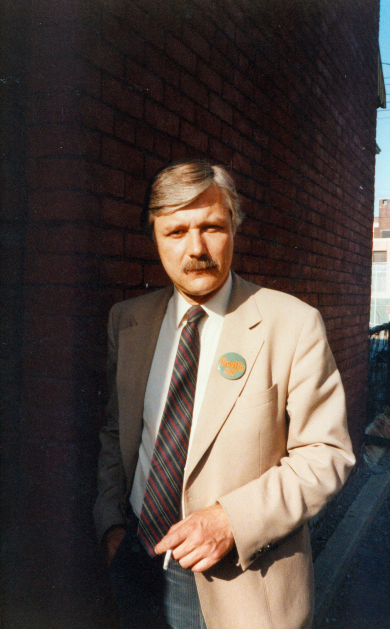 Reville wearing tie and sports jacket with button that reads: Reville NDP