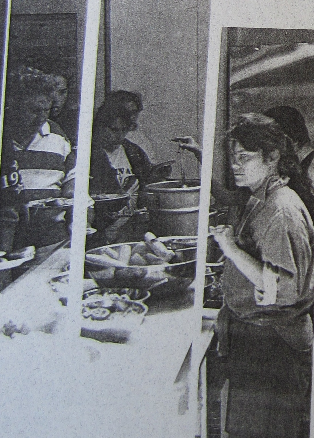 Two women serving food to a line-up of PARC members.