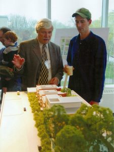 Reville and young man looking at model of housing development