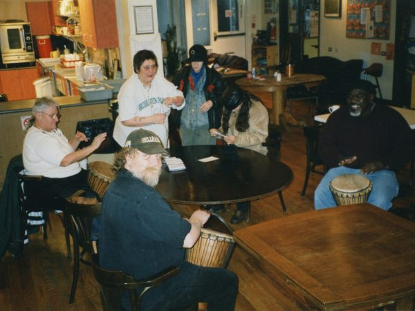 Group of PARC members sitting around a table playing drums