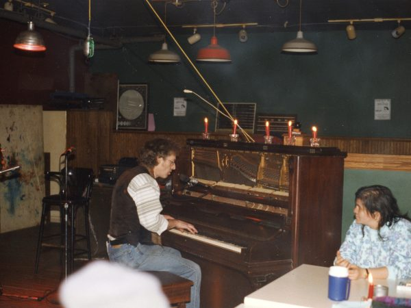 Man playing piano at PARC Drop-In with woman listening at table