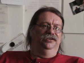 Still photograph of Alex Verkade sitting at his desk at Unity Housing
