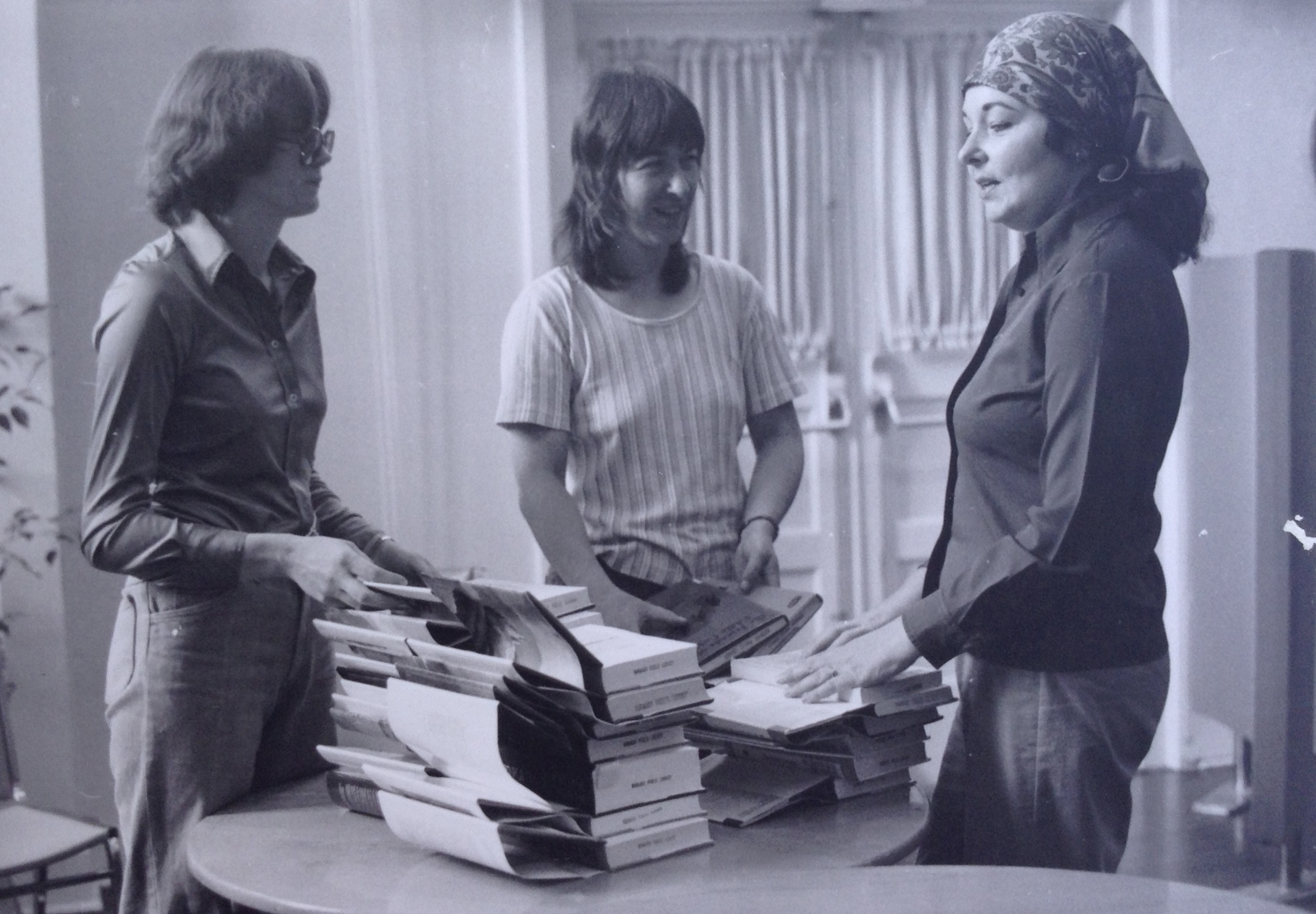 3 women standing together around a table filled with stacks of open library books