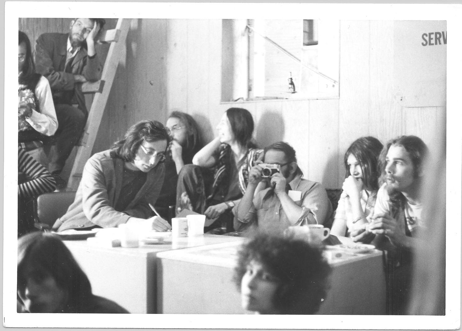 Les premiers membres de l'association MPA regroupés autour d'une grande table. Pedant que Stan Persky tient la caméra, Lanny Beckman est au bout de la table en train d'écrire