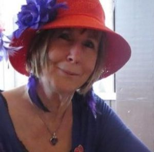 middle aged woman smiling, wearing beautiful red hat