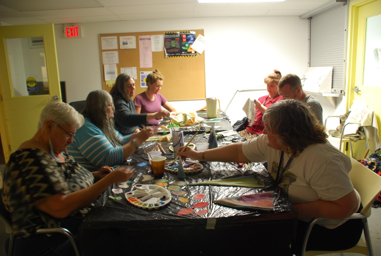 Groupe de sept participants à l'atelier, assis atour d'une table avec peinture et tissus.