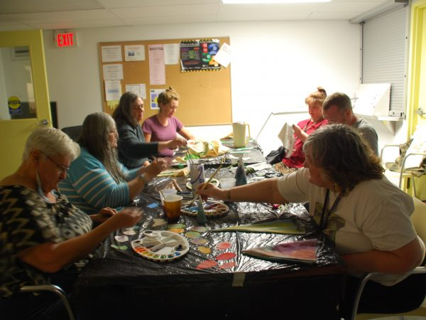 Group of seven Making Room participants sitting around table at creating art with paint and fabric