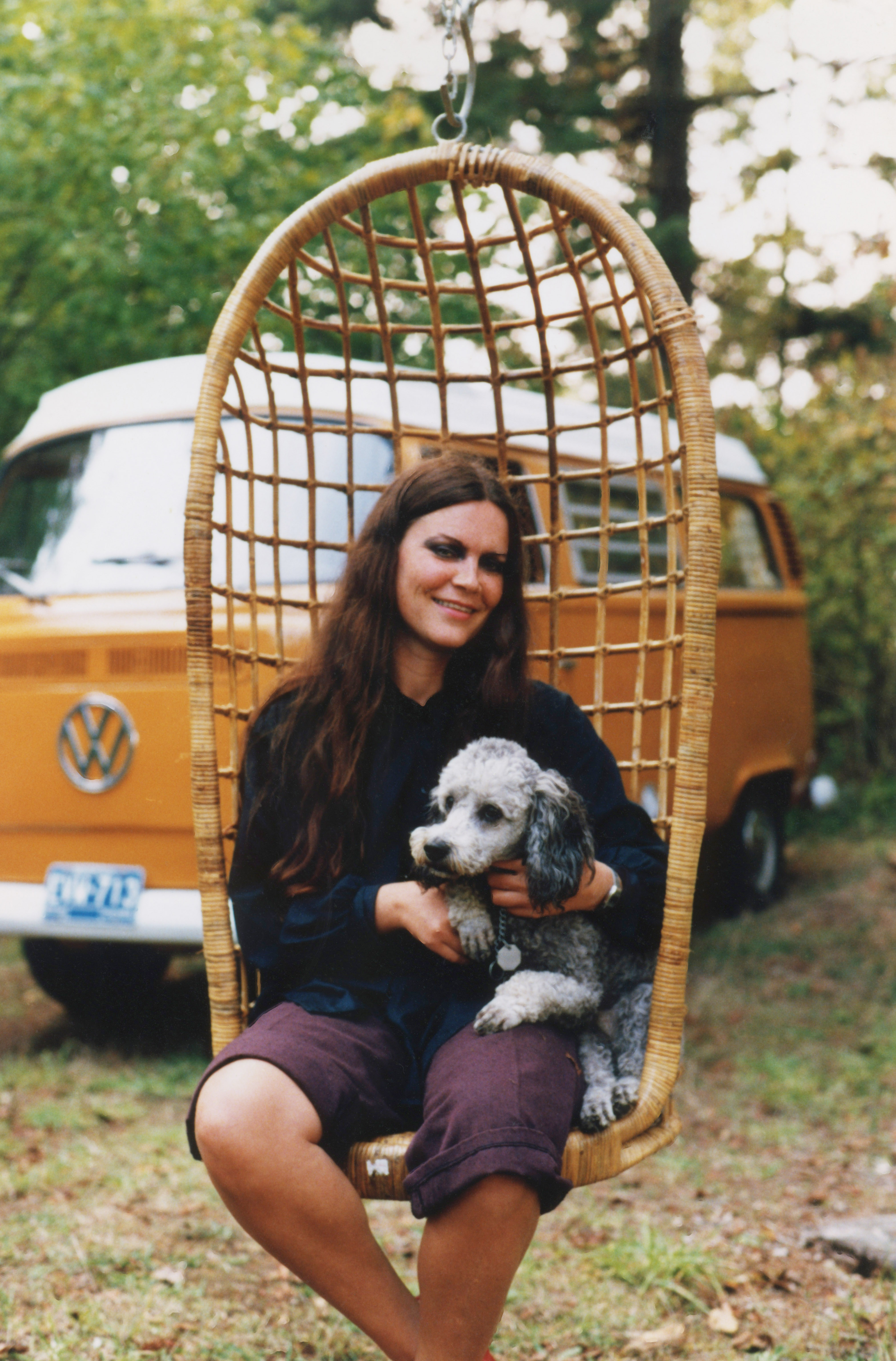 Susan as a young woman sitting in a hanging-basket chair, relaxing with the family dog at the cottage