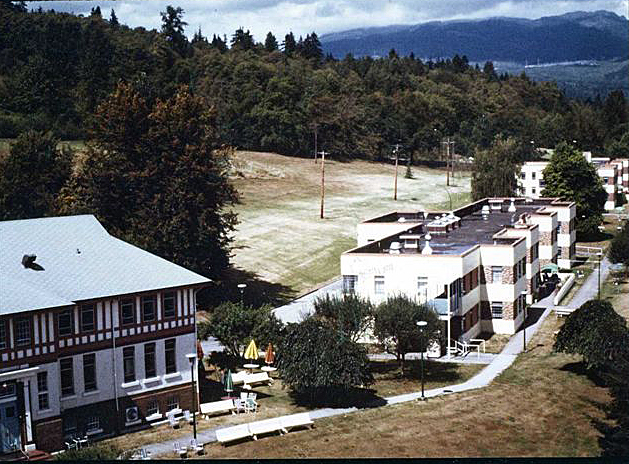 Cluster of institutional buildings on wooded hillside with mountains in the background