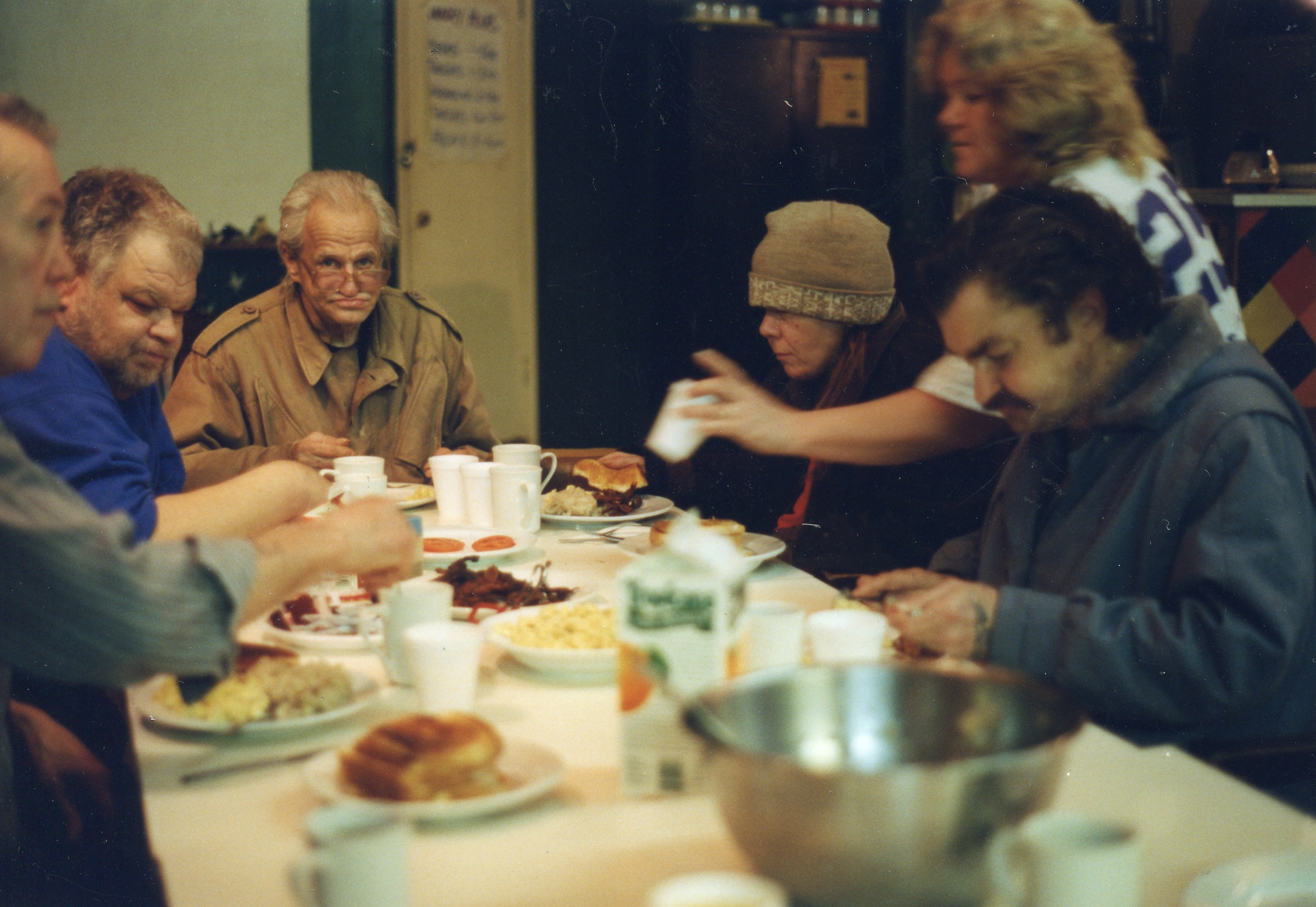 Mealtime photo of group of PARC members sitting around a table eating