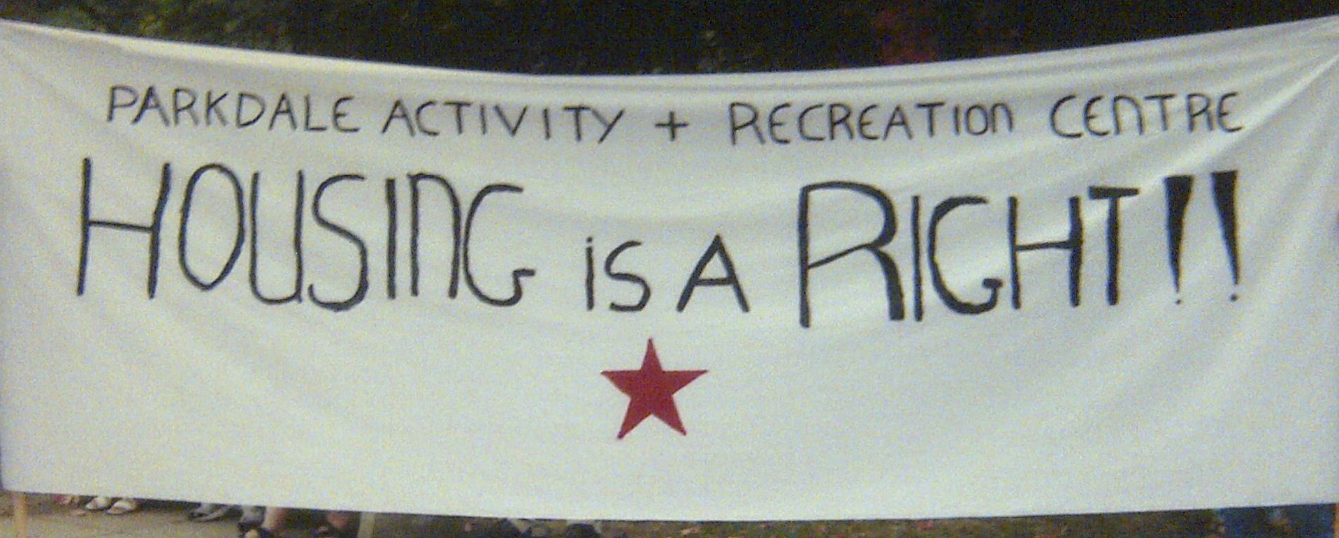 "Photo of banner with ""Parkdale Activity & Recreation Centre"" written across the top and ""HOUSING IS A RIGHT!!"" written below"
