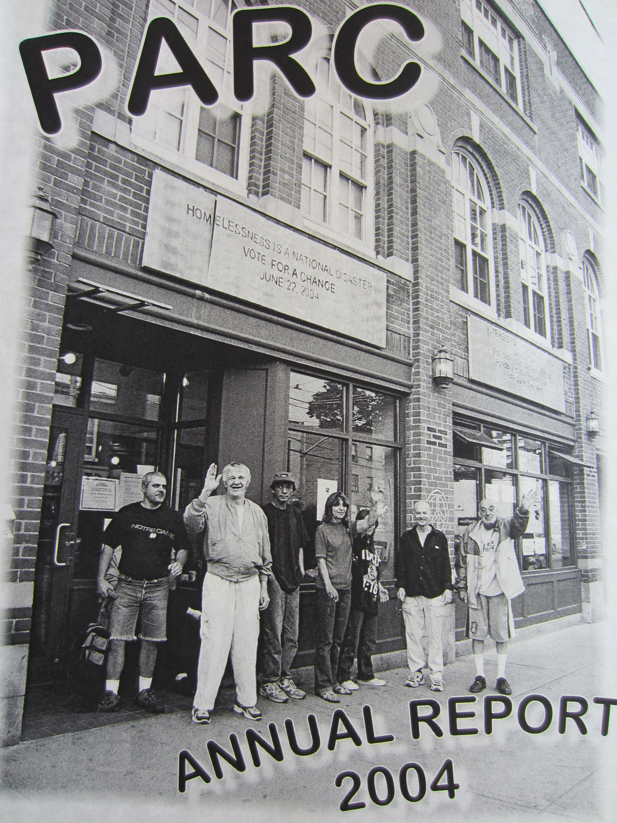 Photograph taken outside the front of PARC with group of seven PARC members waving to the person taking the picture