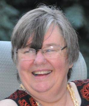 a smiling woman with grey hair and glasses