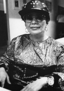 black and white photograph of a woman wearing a baseball cap looking at the camera