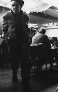 black and white photo of men sitting and standing in area with tables
